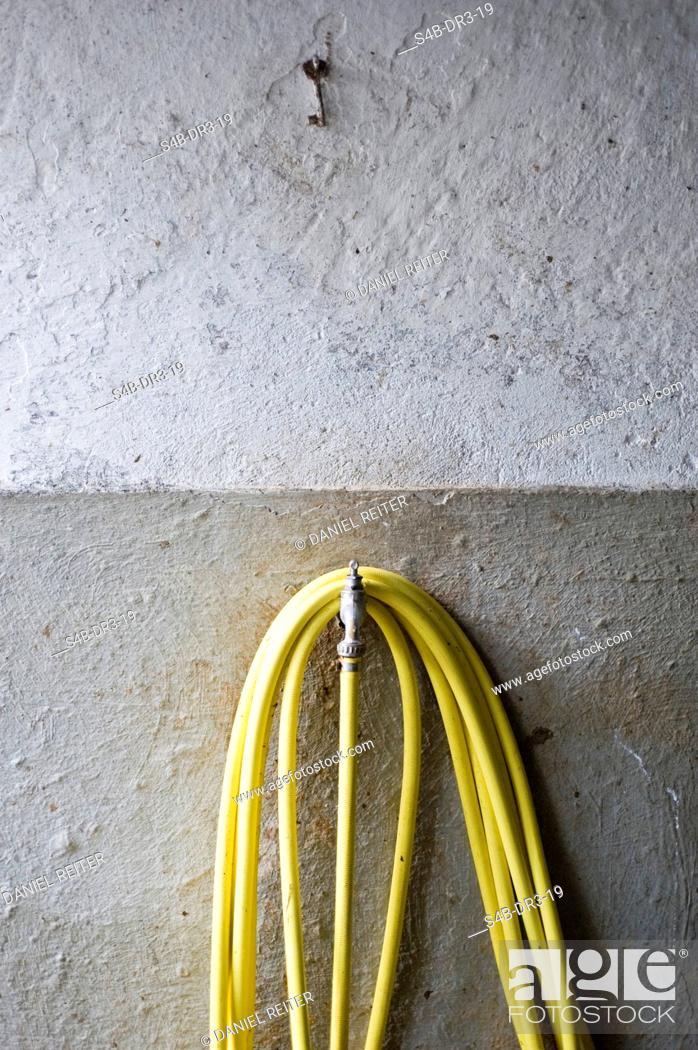 Stock Photo: Water tube and a key at a wall.
