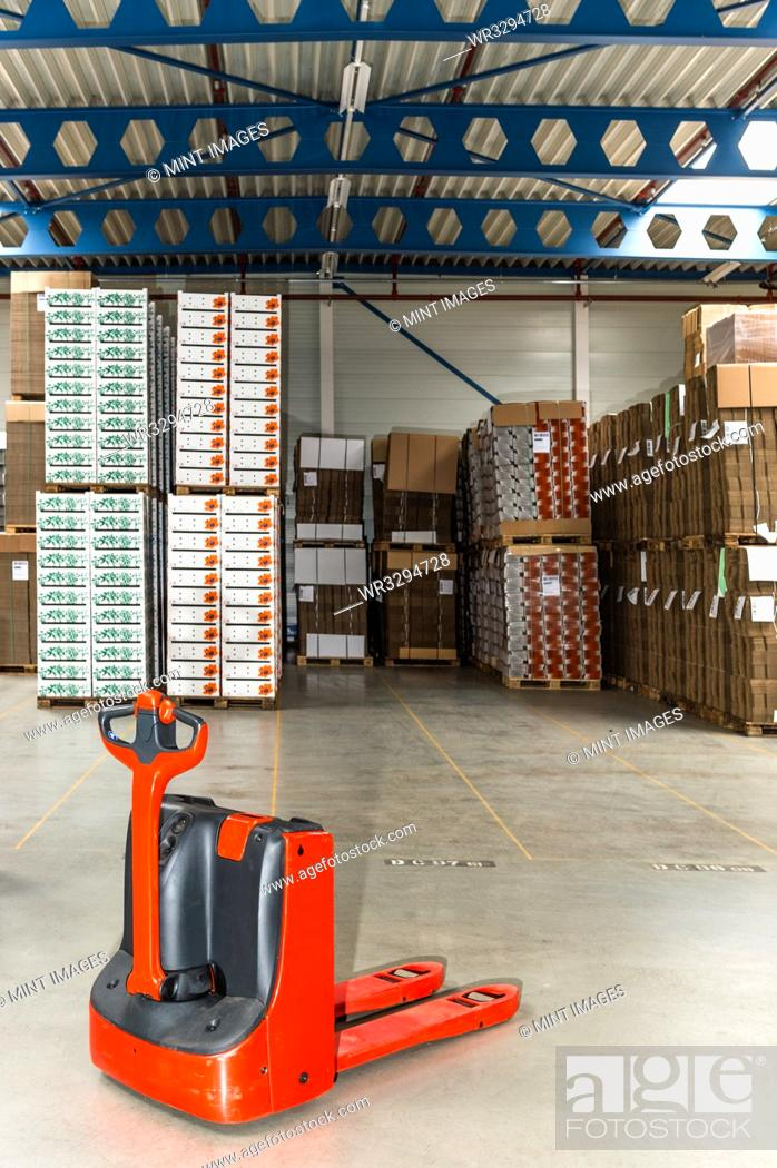 Stock Photo: Mechanical dolly with pallets in warehouse.