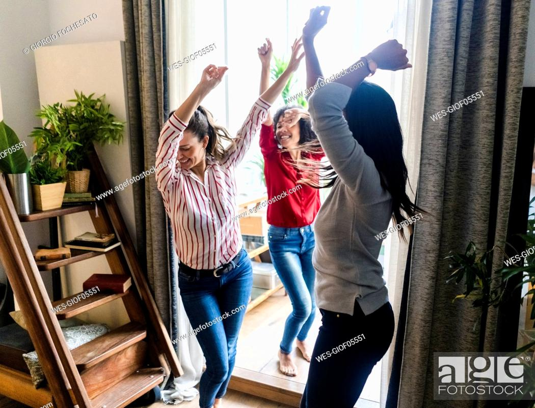 Stock Photo: Three women at home having a party and dancing.