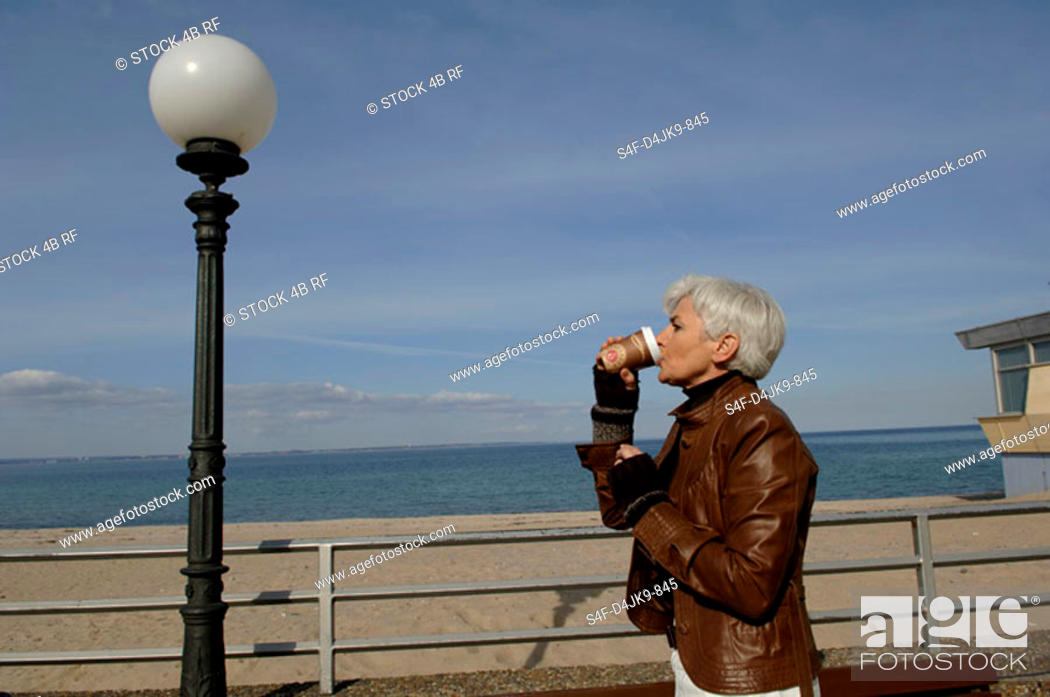Stock Photo: Mature woman drinking a coffee at Baltic Sea beach.