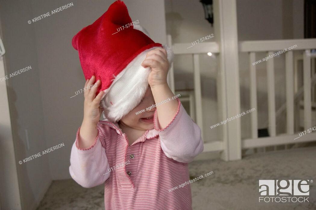 Stock Photo: Toddler girl taking off Santa hat.