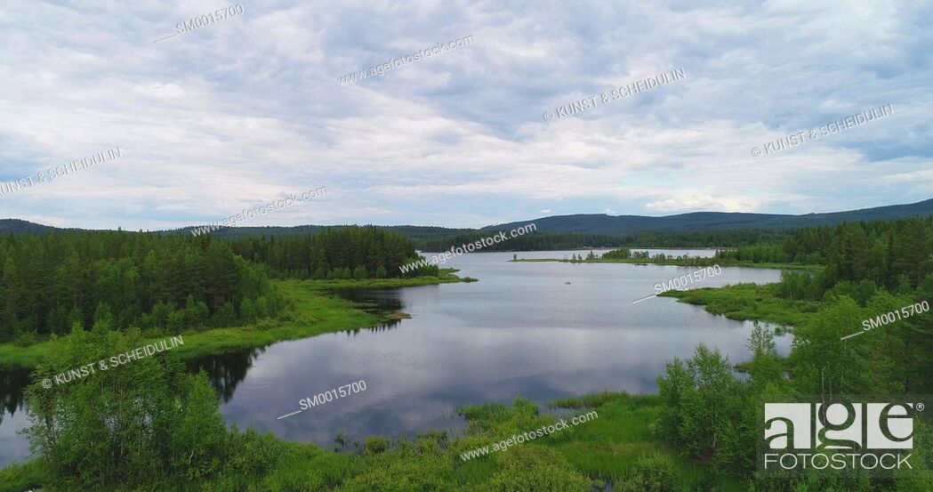 Stock Photo: Clouds are reflected in the glassy water of a forest lake on a summer day in northern Sweden.
