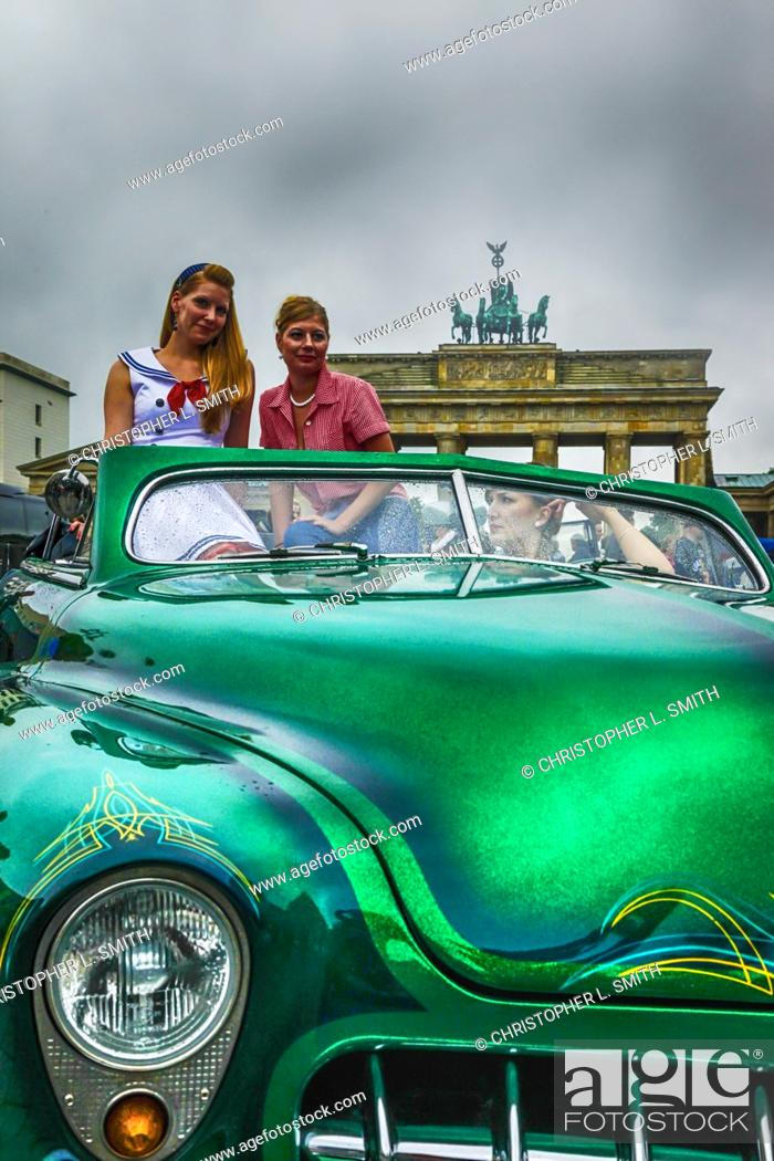 Two Women Sitting In A Green 1950s American Car Pose For