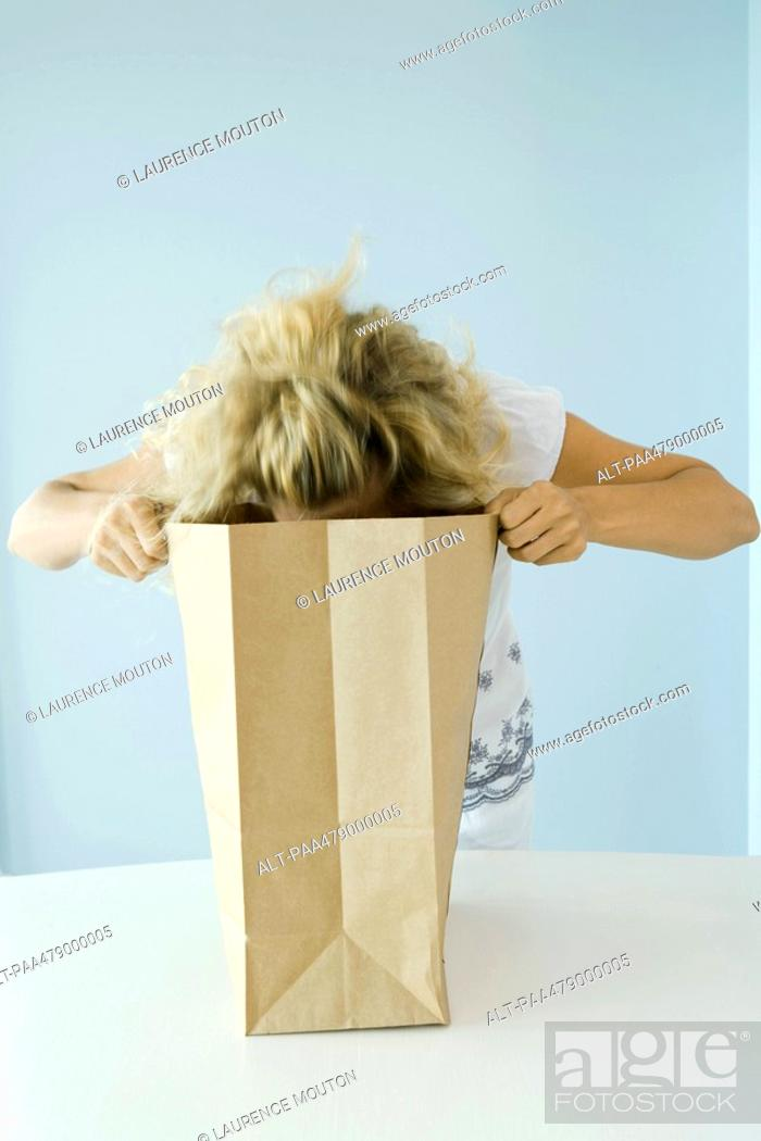 Stock Photo: Woman leaning forward, looking into grocery bag.