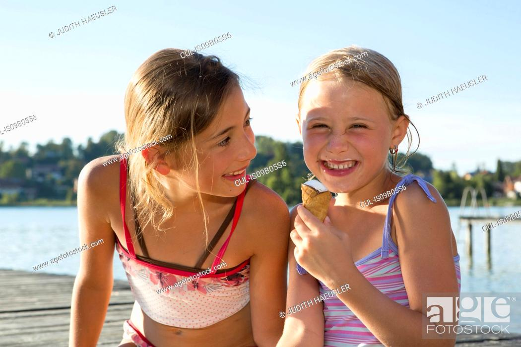 Stock Photo: Two sisters on pier eating ice cream cones, Lake Seeoner See, Bavaria, Germany.