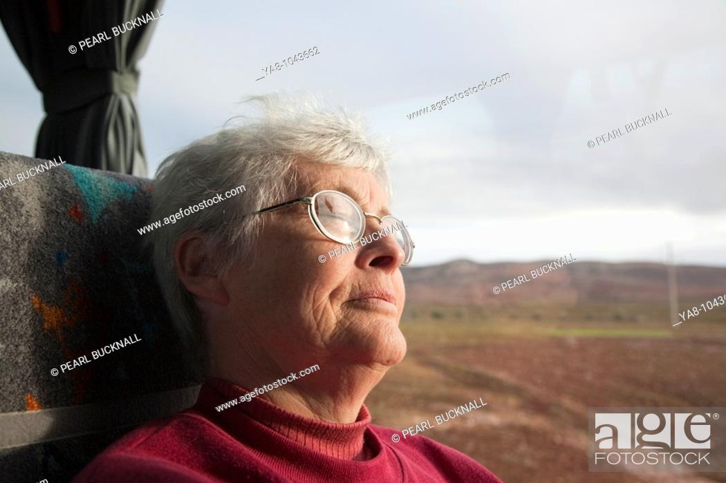Stock Photo: Morocco  Senior woman asleep on coach seat by window MR 08/20.