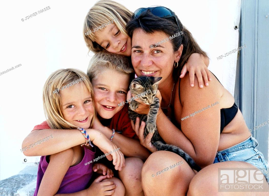 Stock Photo: Portrait of mother with daughters and kitten.