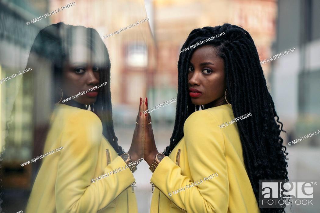 Stock Photo: Young woman wearing yellow blazer, mirrored in a window pane.