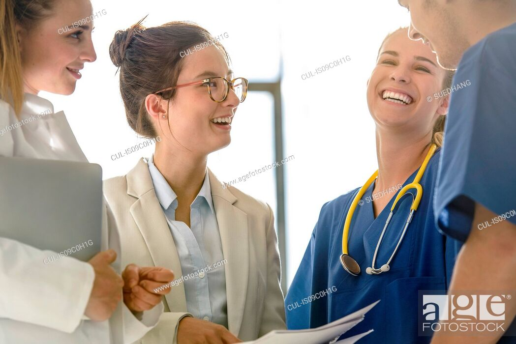 Stock Photo: Young female and male junior doctors chatting and laughing in hospital.