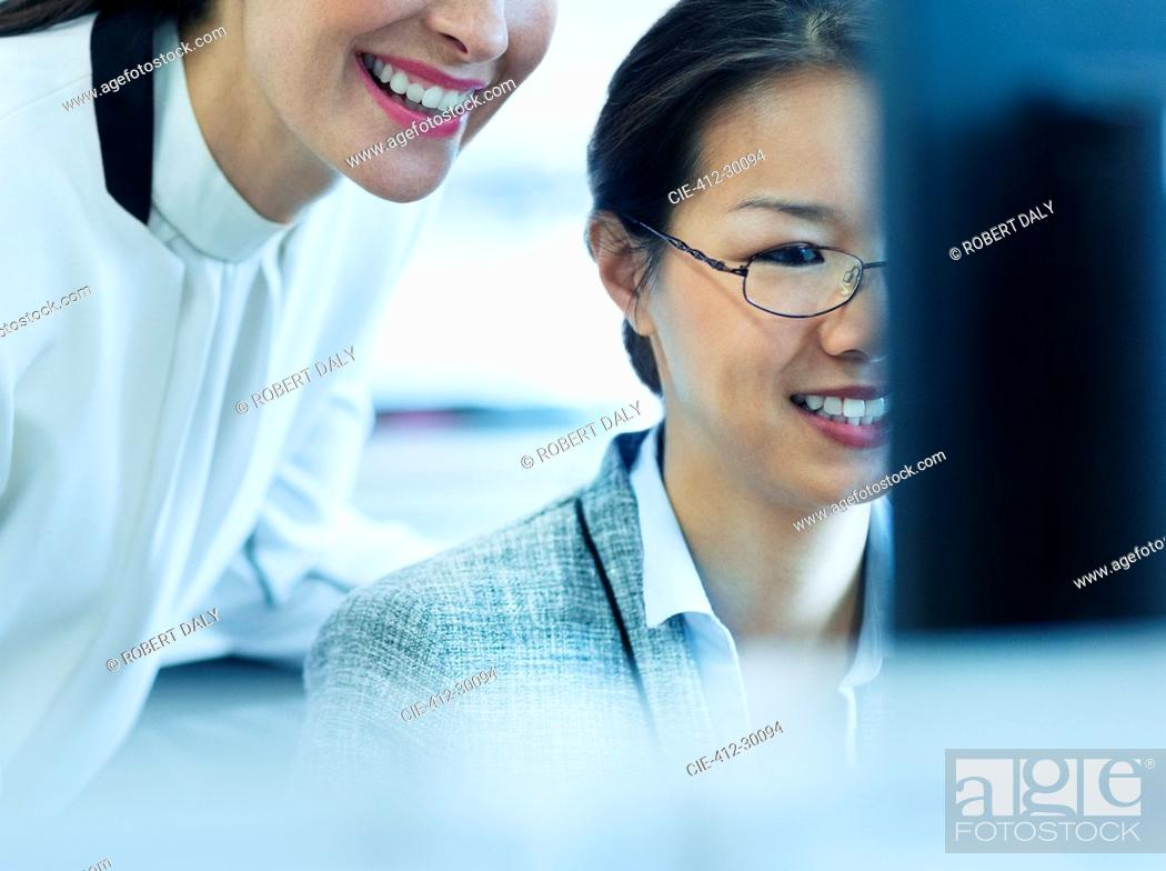 Stock Photo: Smiling businesswomen working at computer in office.