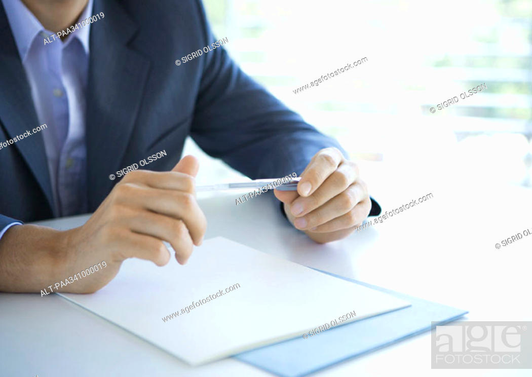 Stock Photo: Businessman holding pen, cropped view of hands.