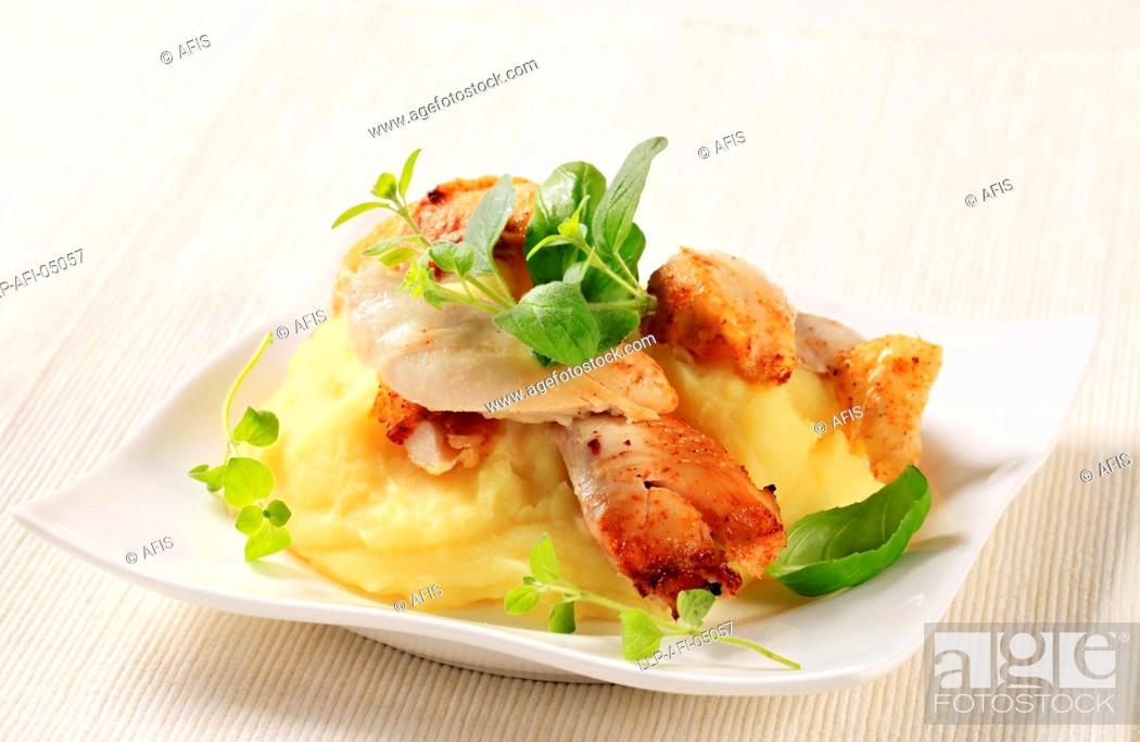 Stock Photo: Pieces of roasted chicken on bed of mashed potato.