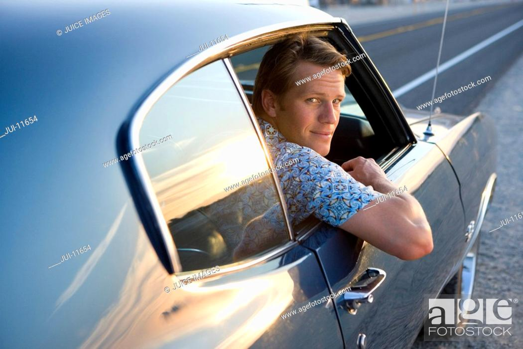 Stock Photo: Young man looking out window of car, portrait.