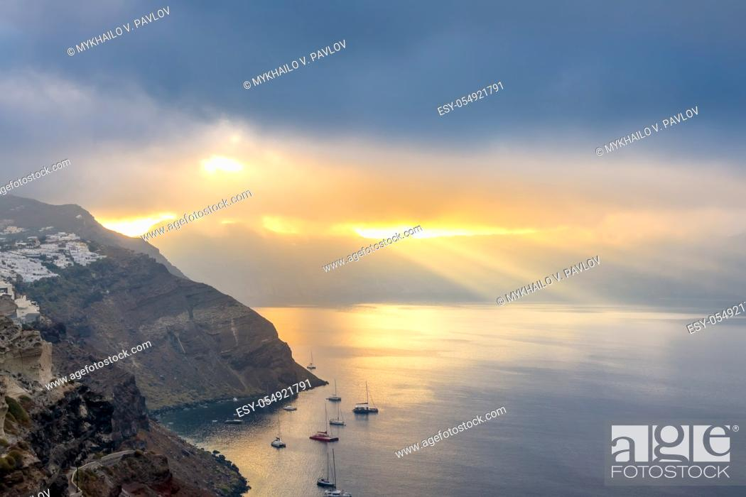 Stock Photo: Greece. Heavy clouds over the caldera of Santorini. Sun Rays illuminates the bay and several anchored yachts.