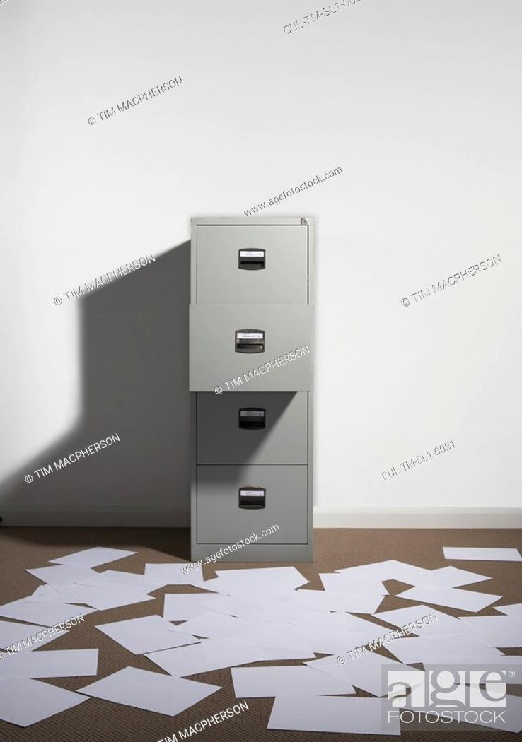 Stock Photo: Filing cabinet against wall with papers strewn about.