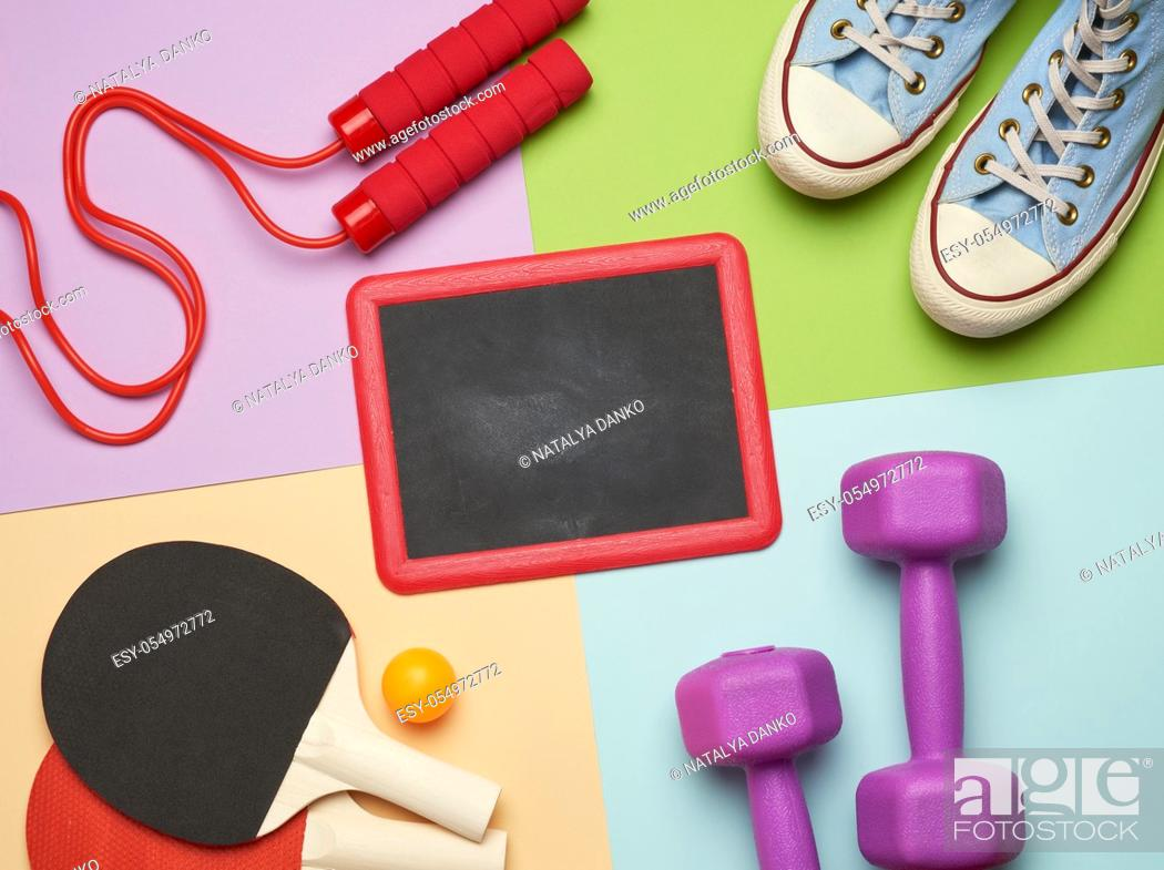Stock Photo: sneakers, jump rope and wooden rackets for table tennis and an empty black chalk board on a colored background, place for an inscription, flat lay.