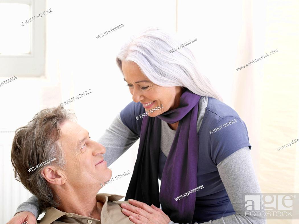 Stock Photo: Germany, Hamburg, Senior couple looking at eachother, smiling.