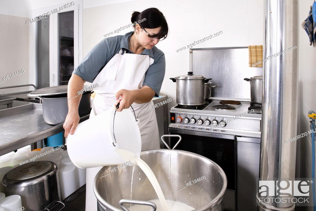 Stock Photo: Cheese Maker pours milk into a steel container to boil it.