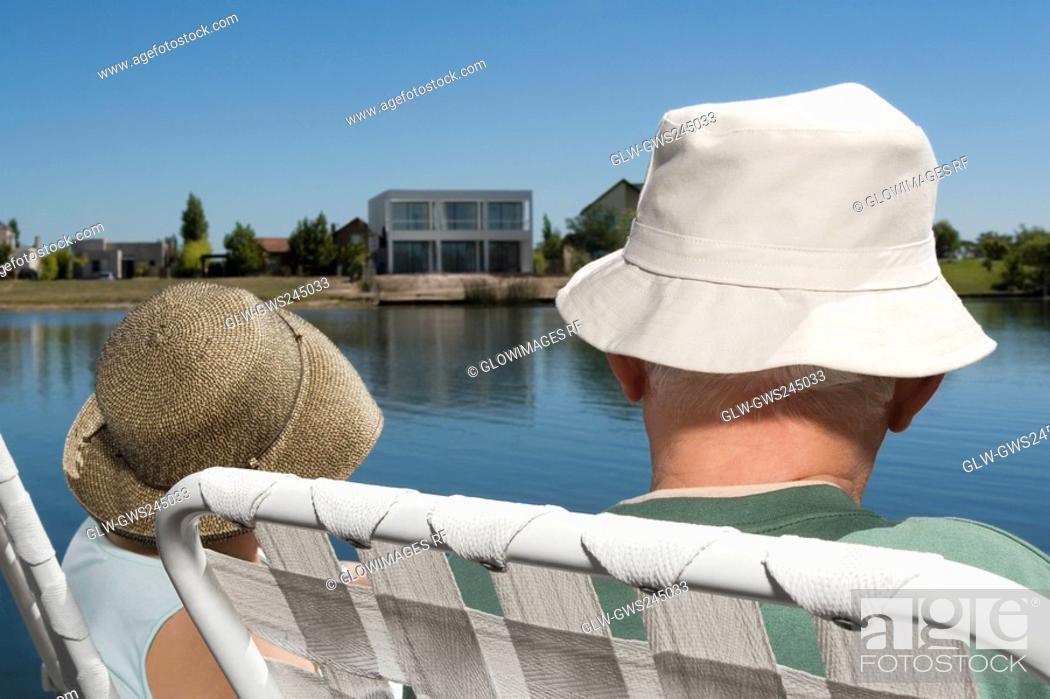 Stock Photo: Rear view of a couple sitting on chairs at the lakeside.