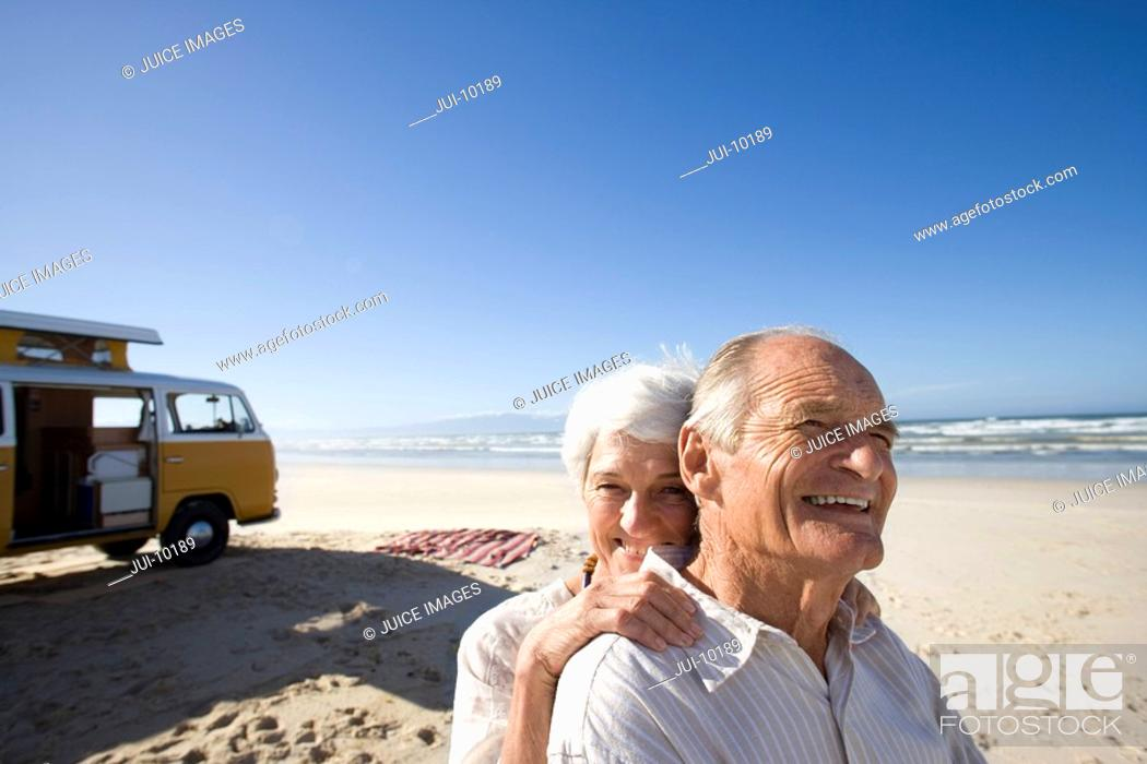 Stock Photo: Senior couple on beach by camper van, woman behind man, smiling, close-up.