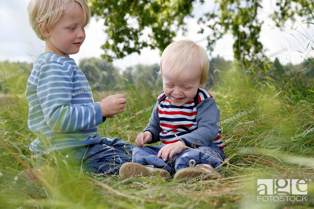 Stock Photo: Two little brothers sitting on a meadow.