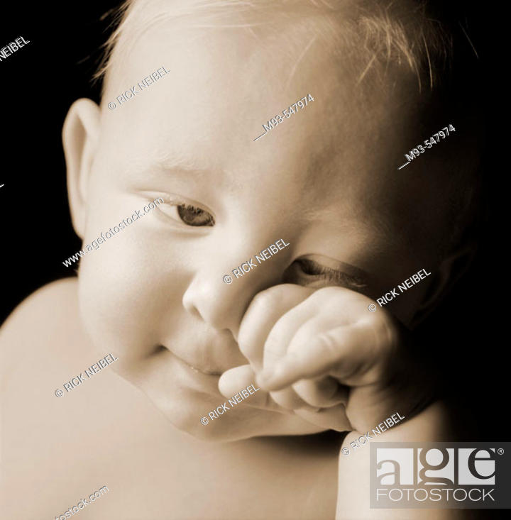 Stock Photo: Caucasian baby, obviously tired, rubbing face. Not crying.