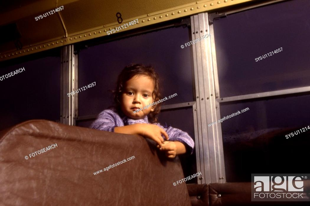 Stock Photo: A small girl poses inside a school bus.