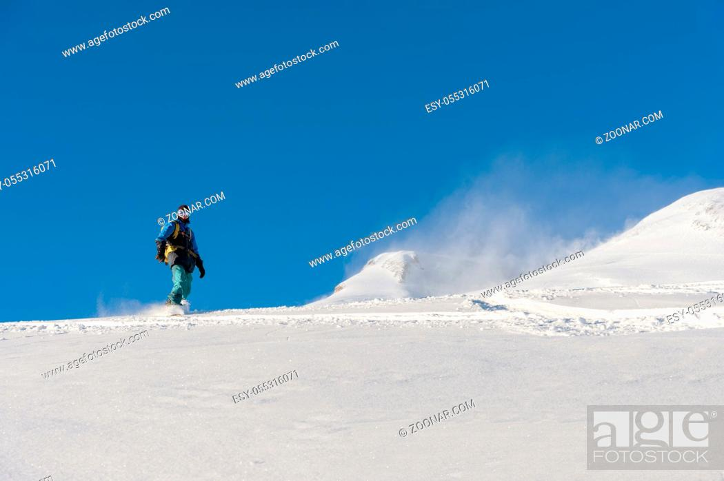 Photo de stock: A freeboard snowboarder in a ski mask and a backpack skates over the snow-covered slope leaving behind a snow powder against the blue sky.
