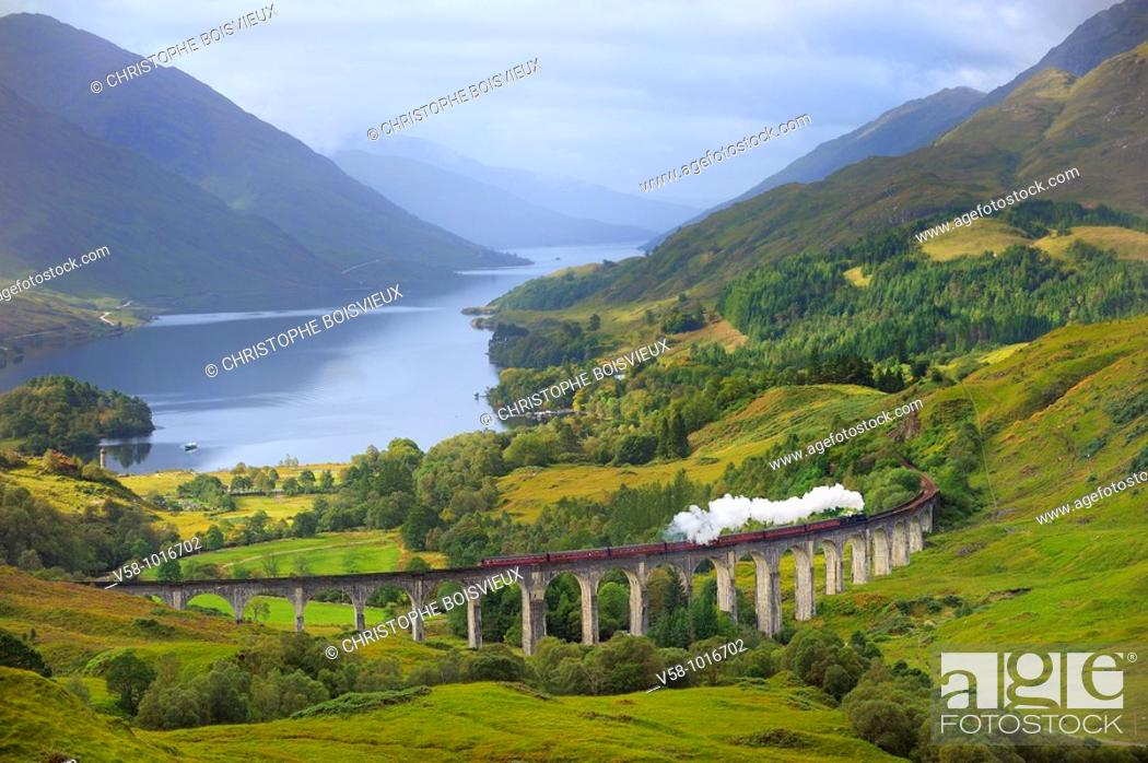 Stock Photo: The Jacobite Steam Train, better known now as the Harry Potter Train, crossing the viaduct of Glenfinnan with loch Shiel in the background. Scotland.