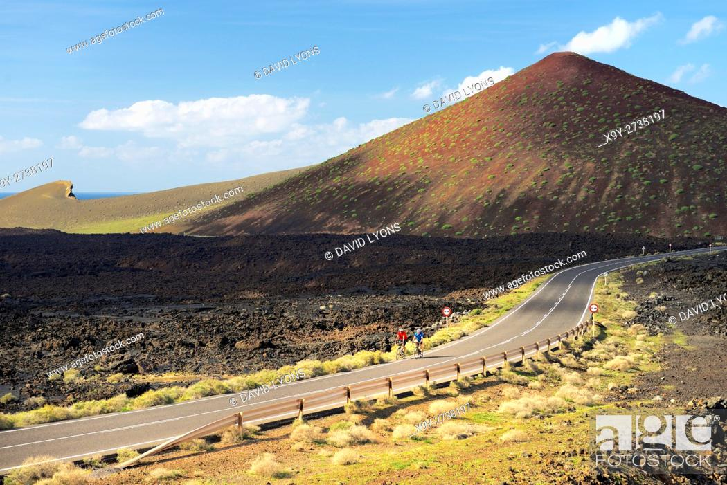 Stock Photo: Cyclists cross lava landscape on the LZ-704 road coming from El Golfo. Timanfaya National Park, Lanzarote, Canary Islands, Spain.
