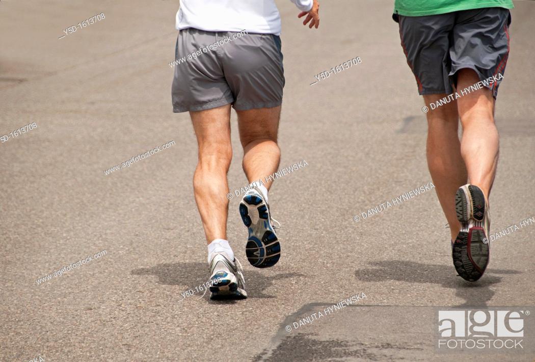 Stock Photo: two men in shorts running the street, legs only, Geneva, Switzerland.
