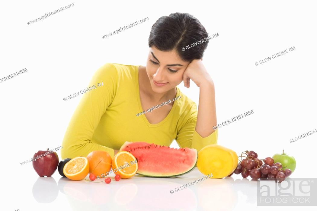 Stock Photo: Woman looking at a row of assorted fresh fruits.