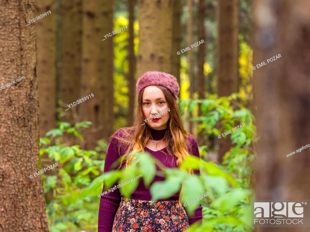 Stock Photo: Close-up young woman in Autumn in a forest looking at camera.