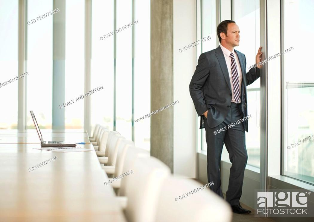 Stock Photo: Pensive businessman standing at window of empty conference room.