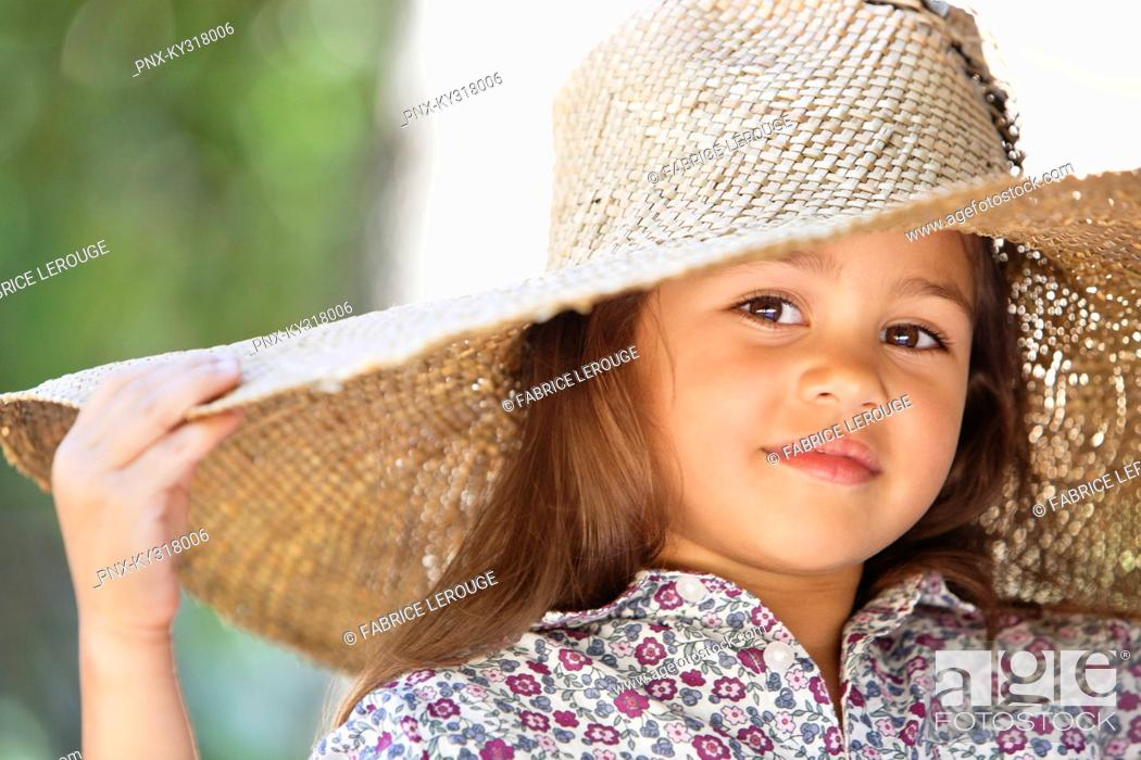 Stock Photo: Portrait of a cute girl wearing a sunhat and smiling.