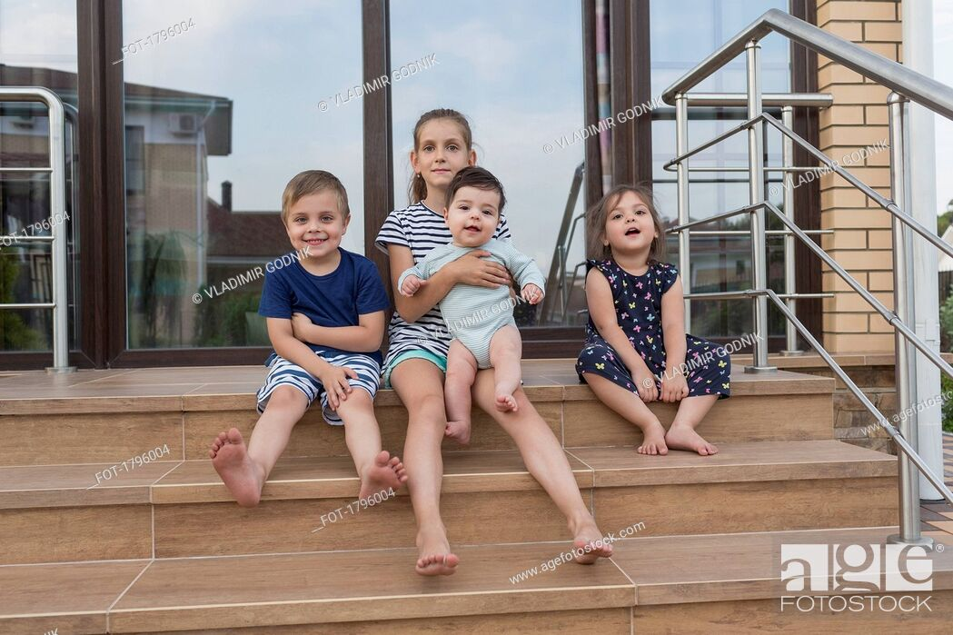 Stock Photo: Portrait barefoot brothers and sisters sitting on patio steps.
