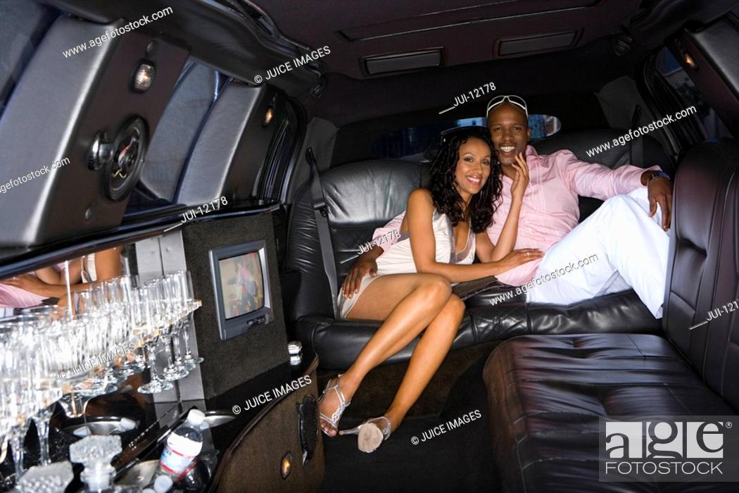 Stock Photo: Young couple in limousine, smiling, portrait.