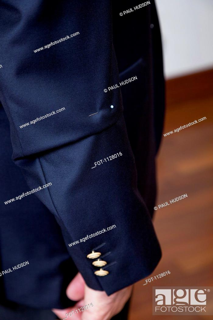 Stock Photo: Detail of a pin in the sleeve of a man's suit jacket.