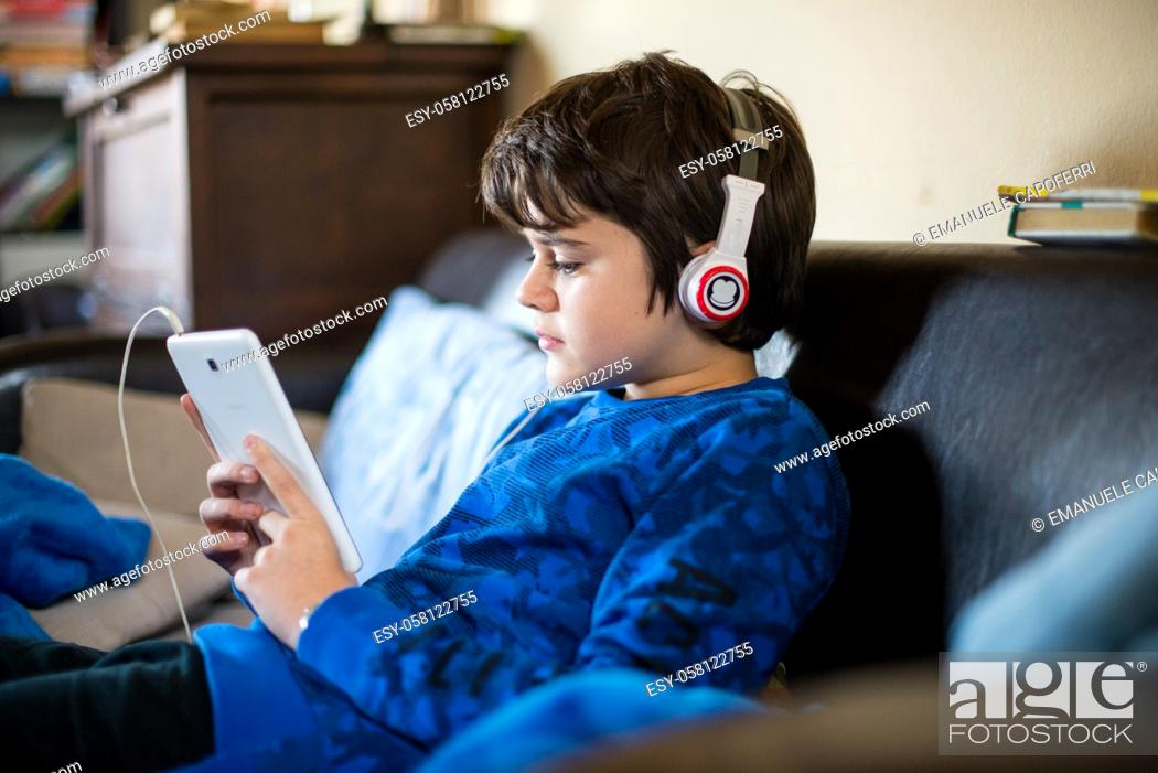 Imagen: boy listens to music from tablet sitting in house-boy watches video on smartphone with headphones.