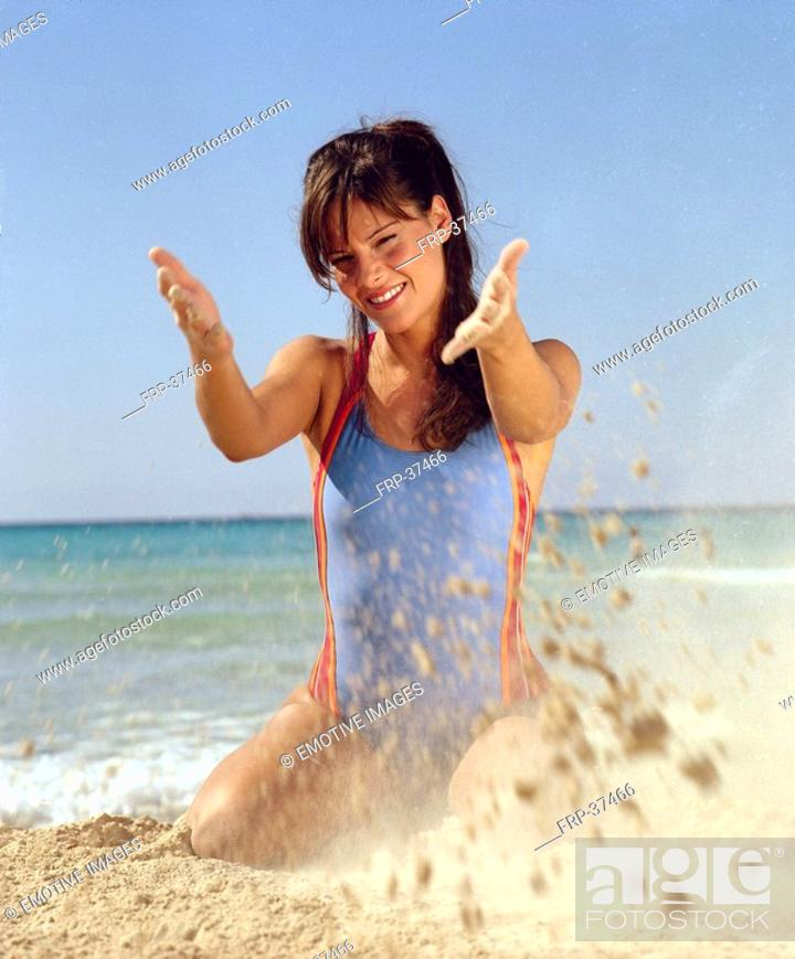Stock Photo: Woman in swimsuit playing with sand.