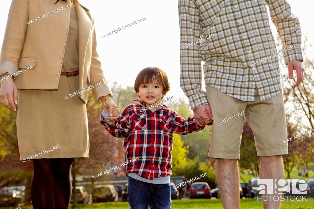Stock Photo: A young boy in between his parents, holding hands.