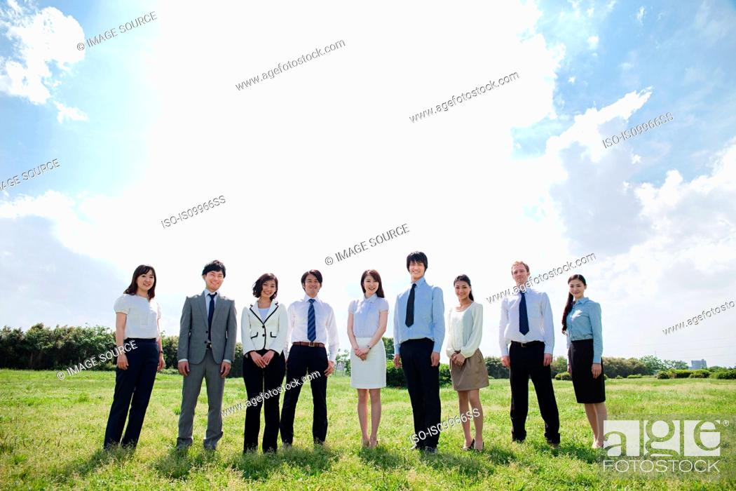 Stock Photo: Businesspeople in a row in field.