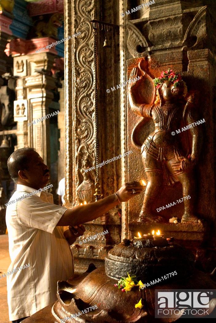 Devotee worshipping lord hanuman bas-relief on pillar in