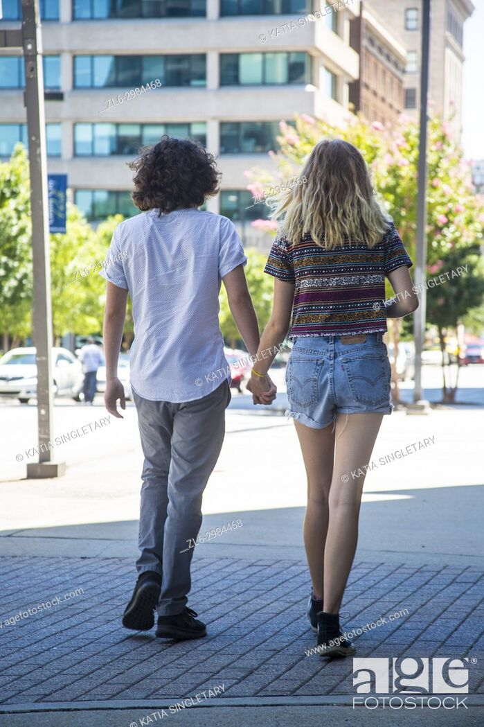 Stock Photo: City, lifestyle photos from the back of a young caucasian Collage couple walking casually hands in hands in the beautiful city of Greensboro with her cafes and.