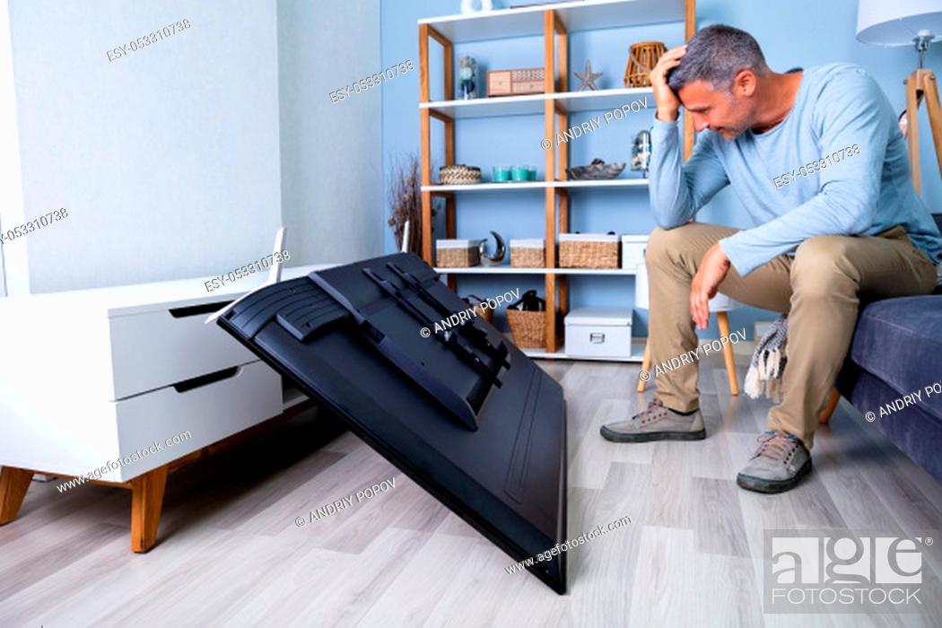 Stock Photo: Man Sitting On Sofa In Front Fallen Television With Broken Screen.