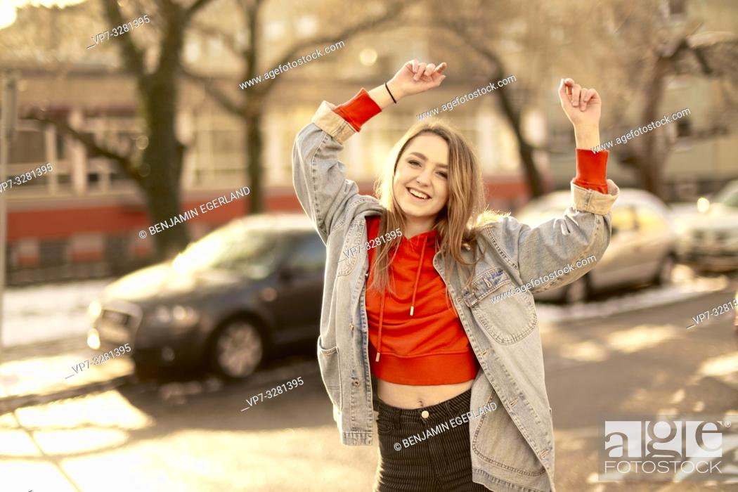 Imagen: young woman dancing on street in city, sunny winter, in Cottbus, Brandenburg, Germany.