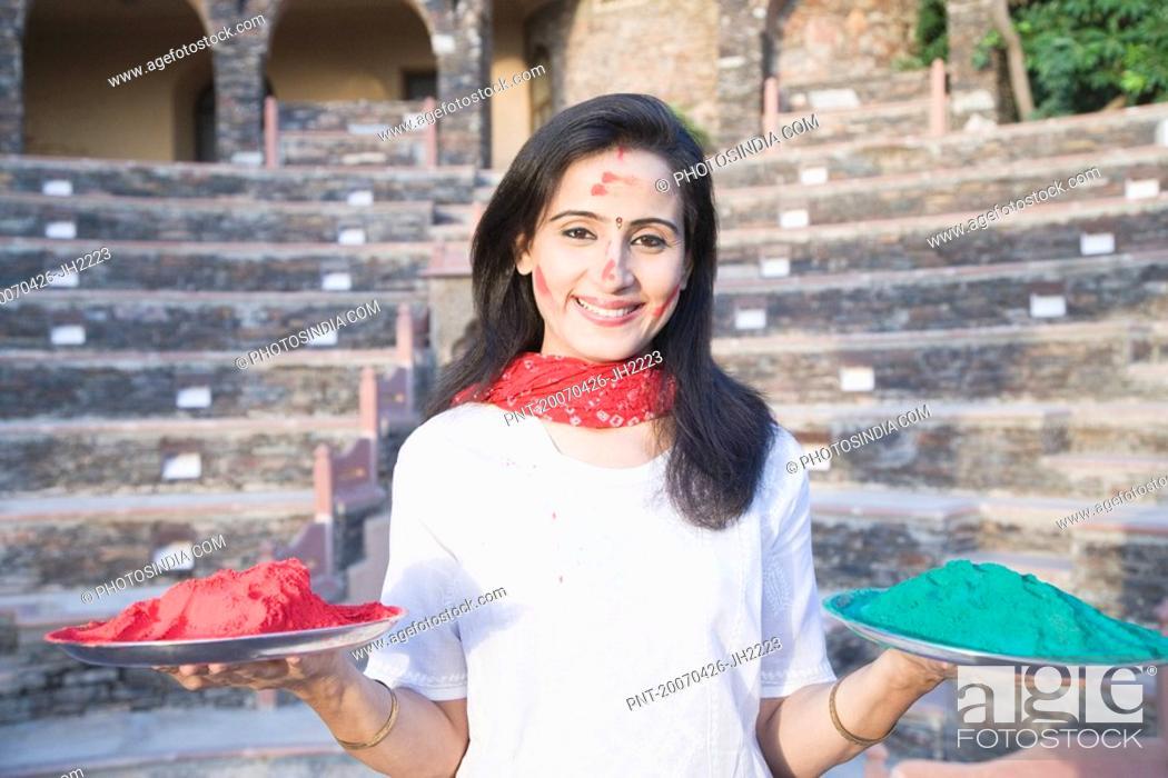 Stock Photo: Portrait of a mid adult woman holding plates of powder paint, Neemrana Fort Palace, Neemrana, Alwar, Rajasthan, India.