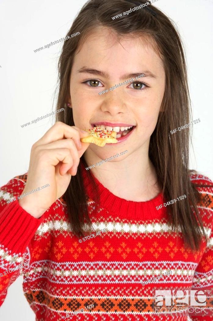 Stock Photo: Girl eating an Christmas cookie.