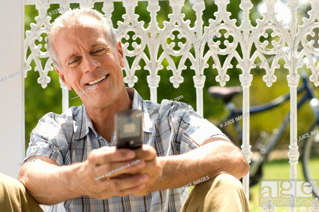Stock Photo: Mature man using mobile phone outdoors, sitting against fence, smiling.