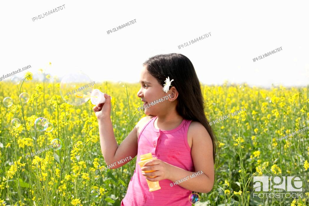 Stock Photo: Young girl making bubbles in a field.